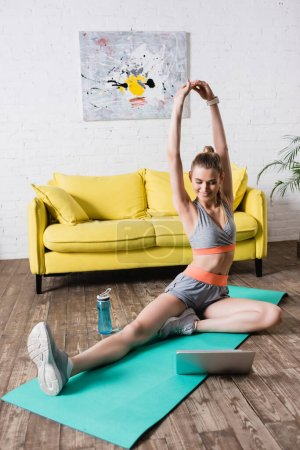 Photo for Smiling sportswoman training near laptop and sports bottle in living room - Royalty Free Image