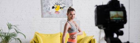 Panoramic shot of sportswoman training near digital camera at home