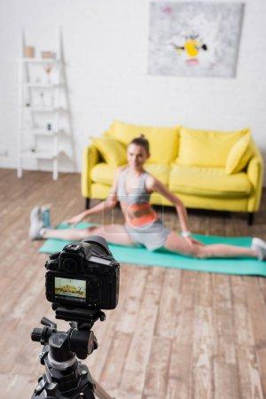 Concentration sélective de la jeune sportive faisant scission sur tapis de fitness près de l'appareil photo numérique à la maison