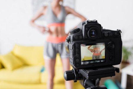 Selektiver Fokus der Digitalkamera in der Nähe von Frauen in Sportbekleidung zu Hause