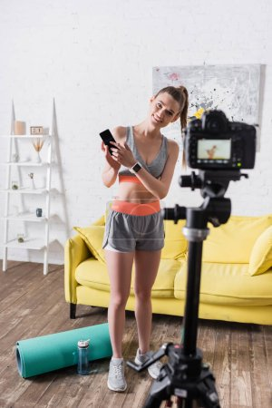 Photo for Selective focus of smiling sportswoman pointing at smartphone near digital camera and fitness mat at home - Royalty Free Image