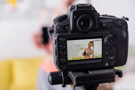 Selektiver Fokus einer lächelnden Sportlerin, die ihr Smartphone mit leerem Bildschirm in der Nähe der Digitalkamera hält