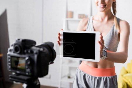 Ausgeschnittene Ansicht einer fröhlichen Sportlerin, die ein digitales Tablet mit leerem Bildschirm an der Digitalkamera zeigt