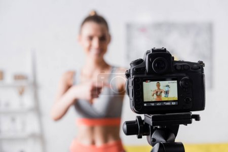 Selective focus of smiling sportswoman pointing at sports bottle near digital camera