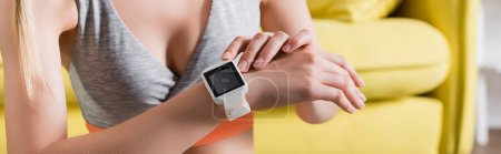 Panoramic crop of sportswoman touching smartwatch at home