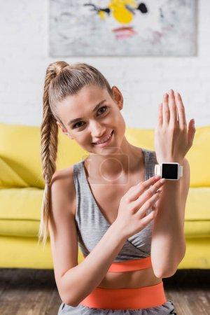 Lächelnde Sportlerin berührt Fitness-Tracker und blickt zu Hause in die Kamera