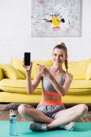 Photo for Smiling sportswoman pointing at smartphone with blank screen while sitting on fitness mat at home - Royalty Free Image