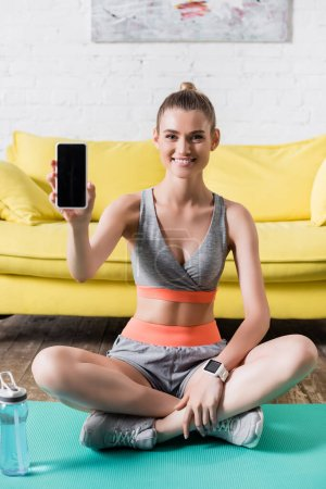 Photo for Positive sportswoman showing smartphone at camera on fitness mat at home - Royalty Free Image