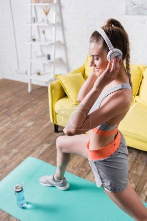 Photo pour Concentration sélective de la sportive souriante dans les écouteurs d'entraînement sur tapis de fitness dans le salon - image libre de droit