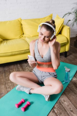 Photo for Smiling sportswoman in headphones using smartphone while sitting on fitness mat at home - Royalty Free Image