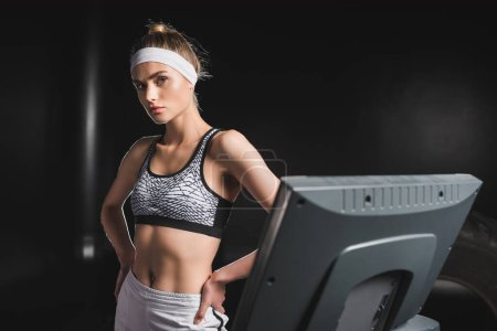 Photo for Selective focus of sportswoman with hands on hips looking at camera near treadmill - Royalty Free Image
