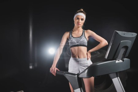 Photo pour Young sportswoman with hand on hip looking at camera on treadmill in gym - image libre de droit