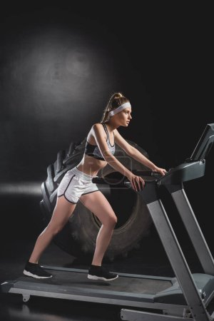 Sportswoman working out on treadmill near tire in gym