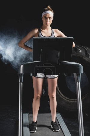 Young sportswoman standing on treadmill near tire in sports center with smoke