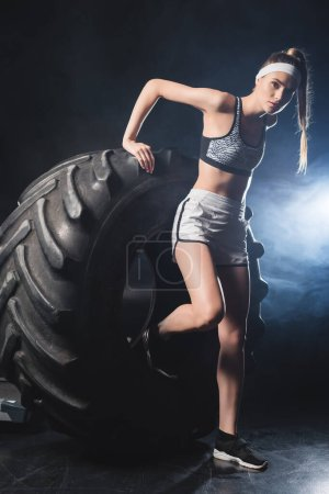 Photo for Sportswoman standing near tire in gym with smoke - Royalty Free Image