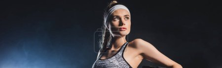 Photo pour Panoramic shot of sportswoman in headband looking away in gym - image libre de droit