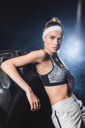 Photo for Young sportswoman in headband looking at camera near tire in gym with smoke - Royalty Free Image