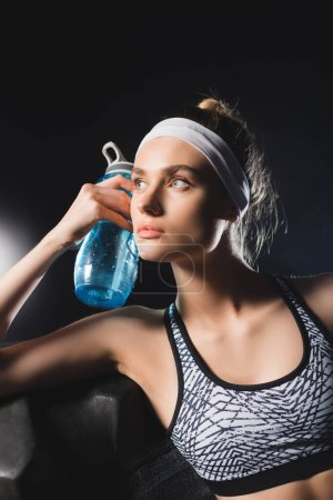 Photo for Selective focus of young sportswoman holding sports bottle near tire in gym - Royalty Free Image