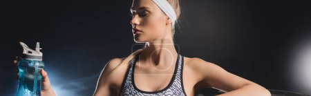 Panoramic orientation of sportswoman holding sports bottle in gym with smoke