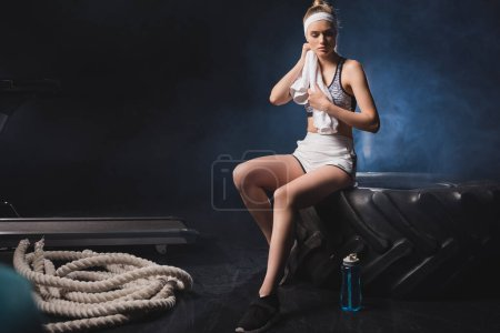 Selective focus of sportswoman holding towel while sitting on tire near sports bottle and battle rope in gym with smoke