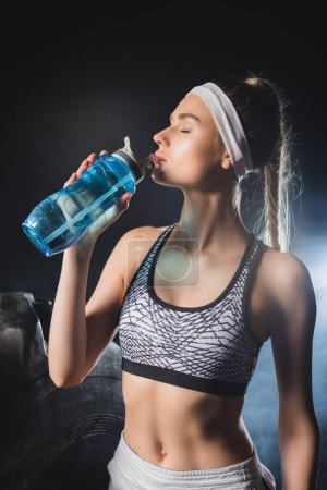 Photo pour Sportswoman drinking water near tire in gym with smoke - image libre de droit