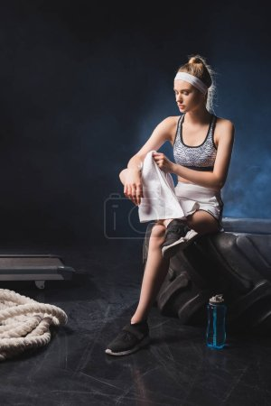 Photo for Sportswoman holding towel while sitting on tire near battle rope in sports center with smoke - Royalty Free Image