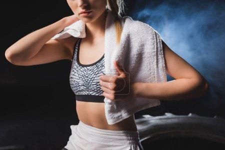 Cropped view of young sportswoman holding towel in sports center with smoke