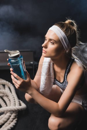Photo pour Concentration sélective de la sportive avec serviette tenant bouteille de sport près de la corde de combat dans la salle de gym avec de la fumée - image libre de droit