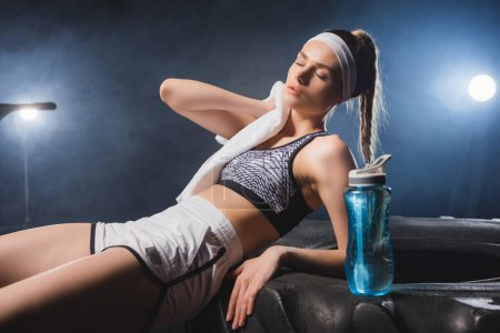 Photo for Exhausted sportswoman wiping neck with towel near sports bottle on tire in gym with smoke - Royalty Free Image
