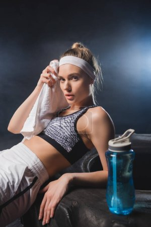 Selective focus of sportswoman holding towel near sports bottle on tire in gym