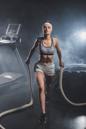 Foto de Joven deportista entrenando con cuerda de batalla cerca de la cinta de correr y neumático en gimnasio con humo - Imagen libre de derechos