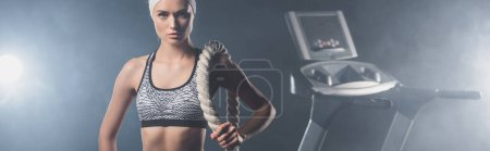 Panoramic shot of sportswoman looking at camera while holding battle rope near treadmill in gym with smoke