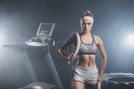 Sportswoman holding battle rope near treadmill and tire in gym with smoke