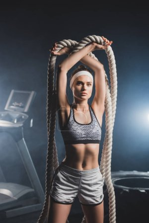Photo for Young sportswoman looking at camera while holding battle rope in sports center with smoke - Royalty Free Image