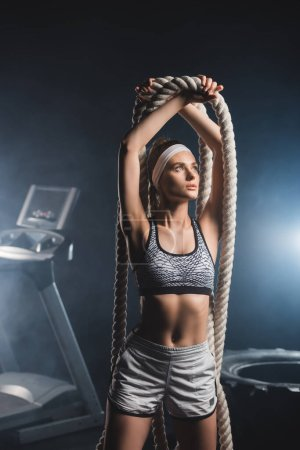 Sportswoman holding battle rope while standing in gym with smoke