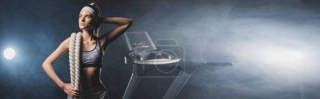 Photo pour Récolte horizontale de sportive tenant une corde de combat près du tapis roulant dans un centre sportif avec de la fumée - image libre de droit