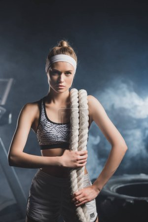 Young sportswoman with battle rope looking at camera in sports center with smoke
