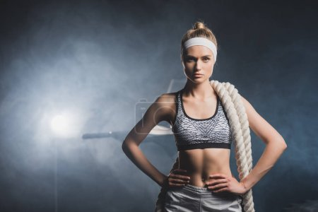 Sportswoman in headband with battle rope looking at camera in gym with smoke