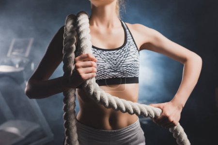 Photo pour Cropped view of young sportswoman holding battle rope in sports center with smoke - image libre de droit