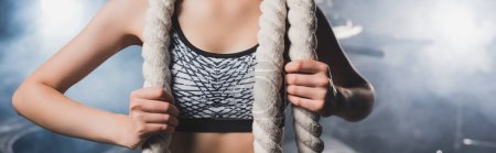 Photo for Panoramic shot of sportswoman holding battle rope near smoke in gym - Royalty Free Image