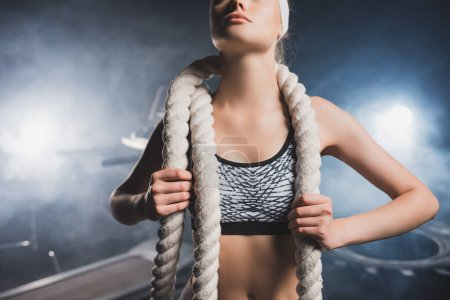 Cropped view of sportswoman in headband holding battle rope in gym with smoke