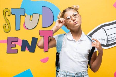 Photo pour Écolière réfléchie touchant lunettes près crayon papier découpé, éléments abstraits et illustration étudiante sur jaune - image libre de droit