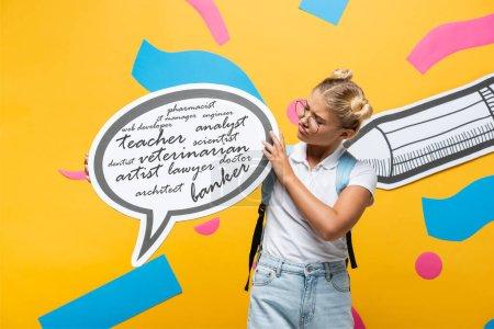 Photo pour Écolière sceptique tenant bulle de parole avec des professions lettrage près crayon de papier et des éléments abstraits sur jaune - image libre de droit