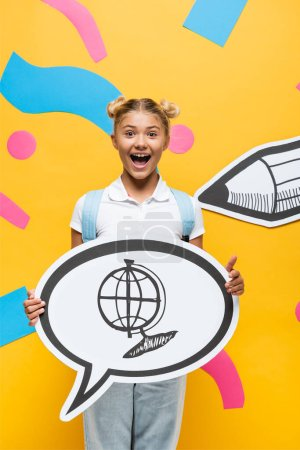 excited schoolchild holding speech bubble with globe illustration near paper elements and pencil on yellow
