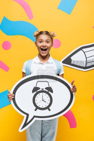 excited schoolchild holding speech bubble with alarm clock illustration near paper elements and pencil on yellow
