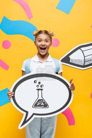 Photo pour Écolier excité tenant la bulle de parole avec illustration de tube à essai près des éléments en papier et crayon sur jaune - image libre de droit