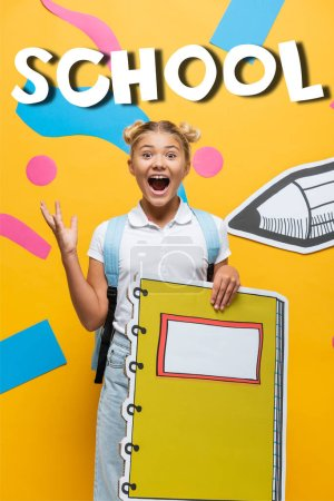 Photo for Excited schoolgirl with notebook maquette gesturing near decorative elements, school lettering and paper cut pencil on yellow - Royalty Free Image