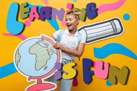 joyful schoolgirl holding globe maquette near learning is fun lettering, paper pencil and abstract elements on yellow