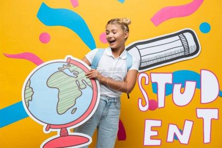 alegre colegiala celebración globo maqueta cerca estudiante lettering, papel lápiz y abstracto elementos en amarillo