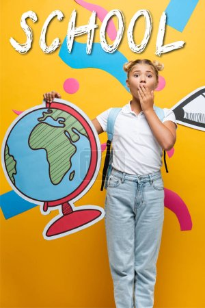 shocked schoolgirl covering mouth while holding globe maquette near school lettering, paper pencil and decorative elements on yellow